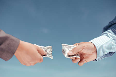 Concept photo of two hands pulling apart money banknote on light blue background