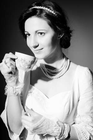 perls: Closeup portrait of drinking tea or coffee beautiful young lady having fun happy smile on copy space background. Black and white photography Stock Photo