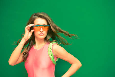 lycra: Portrait of beautiful young woman in pink lycra jumpsuit and plastic protective glass. Sexy lady with curly hair on green wall or screen background. Stock Photo