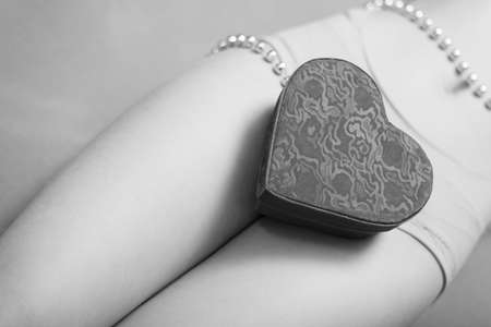 nude young: Closeup picture on present gift box in the form of heart lying on beautiful sexy female legs. Black and white photography Фото со стока