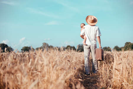 Picture of father holding baby and old suitcase in wheat field. Backview of happy family walking on summer countryside landscape background.
