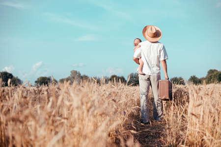 Beeld van de vader die baby en oude koffer in een tarweveld. Backview van gelukkige familie lopen op zomer landschap platteland achtergrond. Stockfoto - 49562618