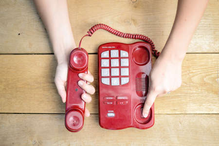 Picture of red cord telephone with big buttons. Closeup of female hands ending conversation on wood plank table background. Stockfoto