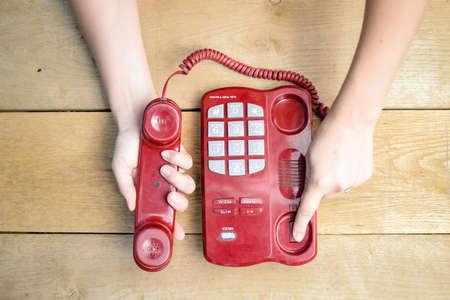 Beeld van rode koord telefoon met grote knoppen. Close-up van vrouwelijke handen die eindigt gesprek op houten plank tafel achtergrond. Stockfoto - 49565561