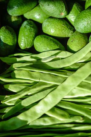 runner bean: Closeup seamless photo of fresh whole avocados above fresh green runner bean rows Stock Photo