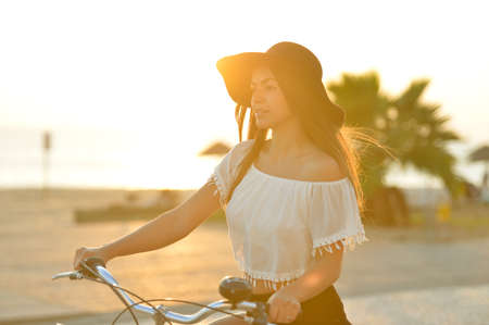 Portrait of attractive amazed brunette with open mouth wearing black hat and white top having fun riding her bicycle along embankment Standard-Bild