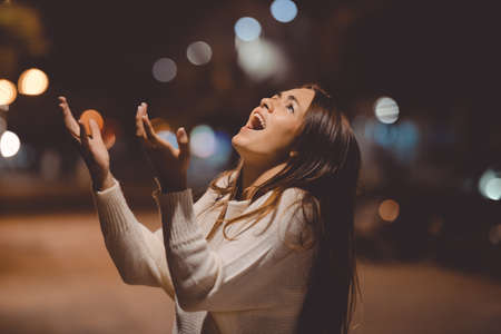bad temper: Closeup portrait of young lady in white sweater holding head and shouting in despair at night on street background