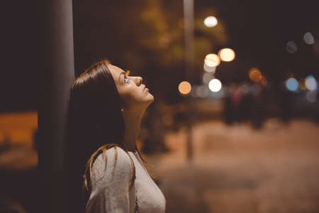 Closeup side view portrait of young sad thoughtful women leaning against street lamp at night on bokeh background