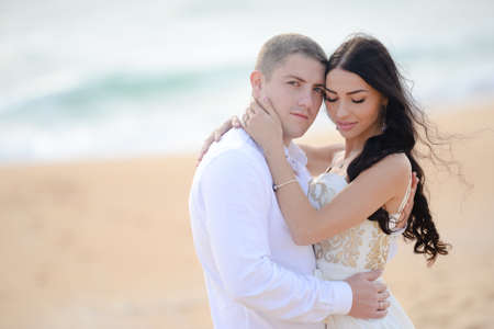 excited man: Happy sunny summer outdoor portrait of young stylish couple while kissing on the beach . Wearing luxury fashion outfits, evening sunlight.