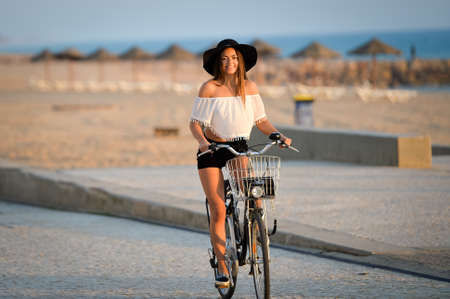 pedals: Photo of excited lady in black hat and white top having joy spinning bicycle pedals in summer on sea embankment background