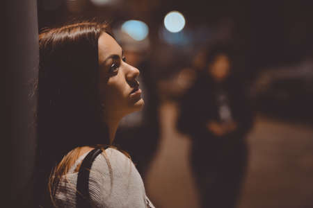 Closeup side view portrait of young sad thoughtful woman leaning against street lamp at night on bokeh background copy space background Stockfoto