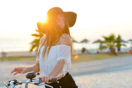 pedals: Photo of excited lady in black hat and white top spinning bicycle pedals in summer on sea embankment copy space background