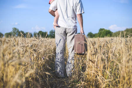 backview: Picture of man holding baby and walking in sunny wheat field. Backview of family with old suitcase on summer rural country background. Stock Photo
