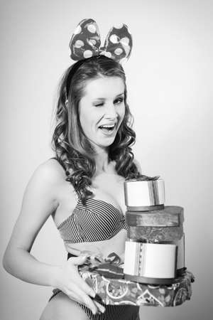 Black and white portrait of romantic sexy young pretty lady having fun emotionally enjoying presents on light copy space background