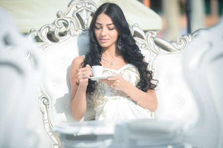 Jeune femme séduisante assis sur le canapé ou une chaise de salon et de boire du café. Portrait de jolie femme sur fond de luxe.