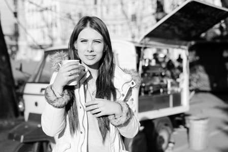 having fun in winter time: Black and white photography of beatiful young woman with a cup of hot drink on sunny outdoors background