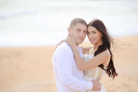 romantic beach: Portrait of beautiful couple kissing at sunset on sandy beach background