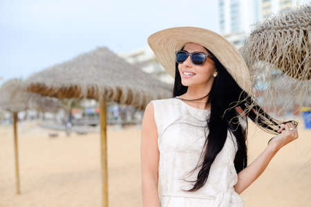 stunningly: Portrait of stunningly beautiful young woman in a white dress and sunglasses. Gorgeous female on beach outdoors background Stock Photo