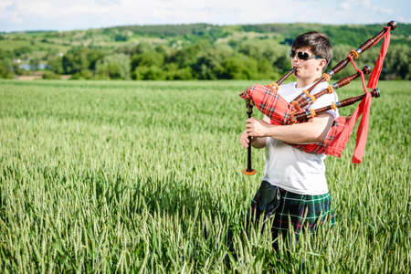 Man enjoying playing pipes in Scotish traditional kilt on green outdoors copy space summer field. Male in sunglasses