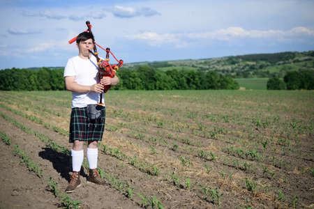 kilt: Portrait of man enjoying playing pipes in Scotish traditional kilt on green outdoors summer field background Stock Photo