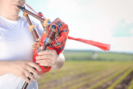 kilt: Closeup view of man enjoying playing pipes in Scotish traditional kilt on green outdoors summer field background