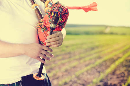 kilt: Close up view of man enjoying playing pipes in Scotish traditional kilt on green field background outdoors