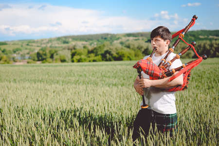 kilt: Man enjoying playing pipes in Scotish traditional kilt on green outdoors copy space summer field.