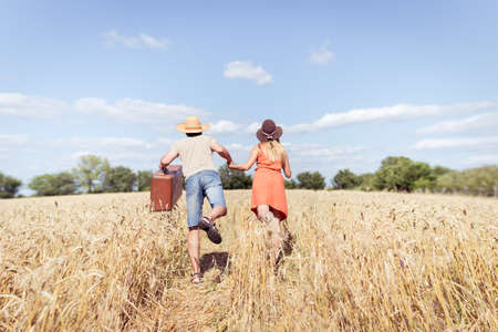 Couple running in field, man holding in his hand vintage suitcase on countryside landscape blue sky outdoors background. Vacation or immigration concept