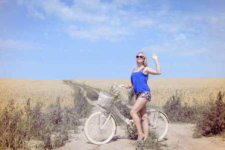 off road biking: Pretty woman with bike on countryside landscape blue sky outdoors background.