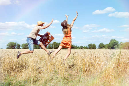 Joyful young couple having fun in wheat field. Excited man and woman jumping with retro leather suitcase on blue sky outdoor background.