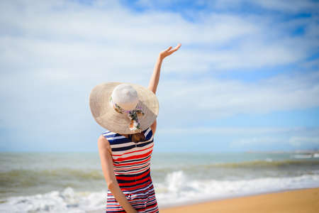 Back view of romantic lady enjoying summer beach and sun, waving at sea. Concept of feeling, freedom, pensive emotional