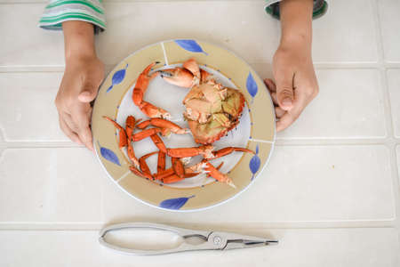 red cooked: Top view picture of hands and red cooked shellfish on plate white table background. Exotic vacation food