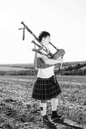 kilt: Black white photography of man enjoying playing pipes in Scottish traditional kilt on outdoors summer field background Stock Photo