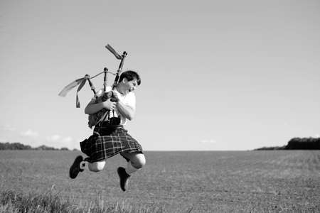 Black and white photography of man jumping high with pipes in Scottish traditional kilt on summer field outdoors background