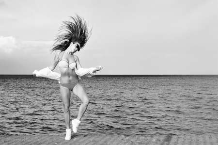 lake beach: Black and white photography of beautiful young lady enjoying dancing jumping over outdoors water sky background. Portrait of sporty girl with long brunette hair blown by the wind and move Stock Photo