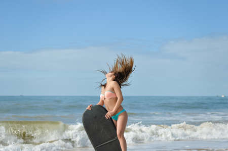 bodyboard: Picture of beautiful girl at the beach with her bodyboard, ready for fun. Beach background sunny blue sky on tropical exotic location Stock Photo