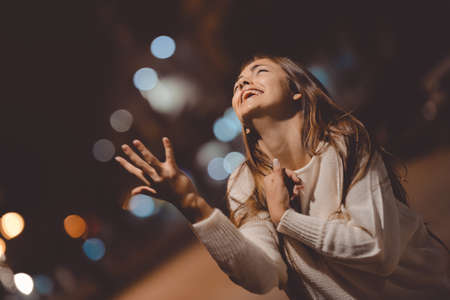 Young emotional stressed woman screaming looking up, city street in the night, evening lights bokeh outdoors background Stockfoto