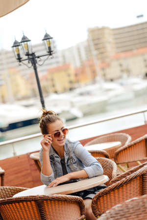 vilamoura: Cheerful happy smiling pretty female in restaurant on luxury marina background. enjoying travel life concept