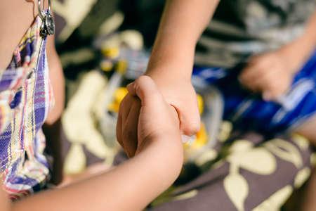 Kids handshake closeup on sunny background outdoors