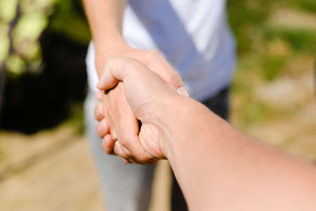 Handshake on outdoors blurred abstract nature background, closeup image