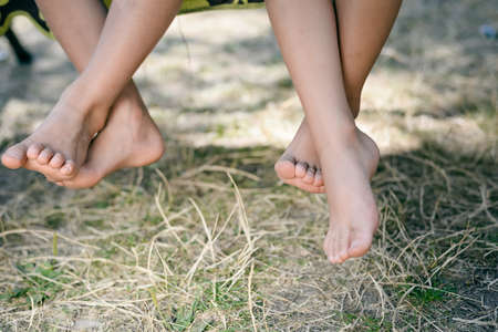 Outdoor picture of two children legs barefoot. Closeup of happy kids sitting on sunny countryside background.