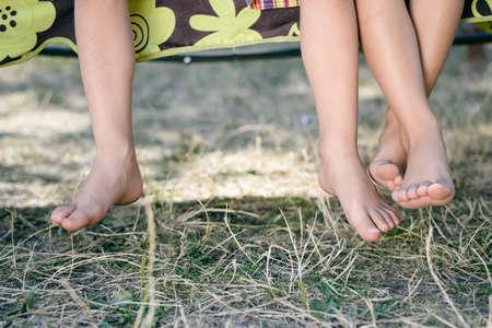 Outdoor foto van twee kinderen benen op blote voeten. Close-up van gelukkige kinderen zitten op zonnige platteland achtergrond. Stockfoto