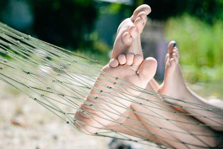 Beeld van volwassenen en kinderen benen op blote voeten. Close-up van gelukkige familie liggend op hangmat op zonnige platteland achtergrond. Stockfoto