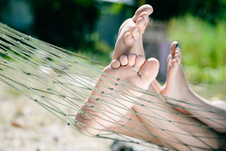 Picture of adult and children legs barefoot. Closeup of happy family lying on hammock on sunny countryside background.