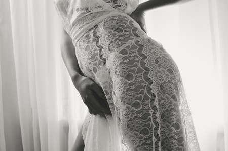modello indossando bianco vedere attraverso abito, primo piano sui fianchi. Femmina su tulle sfondo della finestra