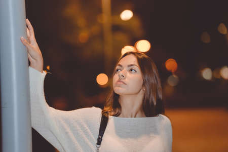 lady with the lamp: Portrait of beautiful young lady, road lamp post in the night, evening lights bokeh background outdoors Stock Photo