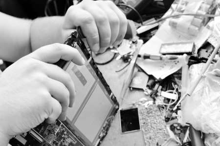 electrical equipment: Black and white photography close up on hands repairing mobile digital device on busy table background Stock Photo