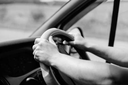 gripping: UK right hand drive car. mans hands gripping wheel, close up black white photography Stock Photo