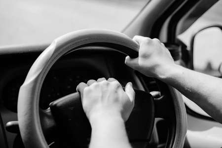 beeping: Black and white photography of hands holding car wheel and beeping a horn, closeup