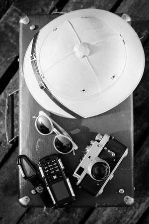 pith: Black white photography top view pith helmet, camera, sunglasses and cellphone on top of retro suitcase. Exploration concept